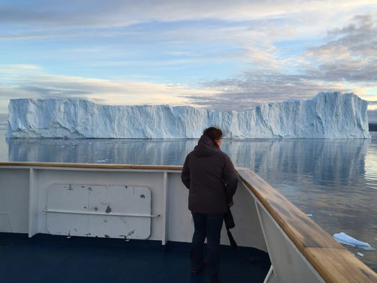 A passenger gazes out over a massive iceberg near the