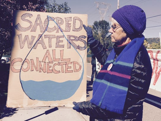 Sister Bette Ann Jaster holds up a protest sign outside