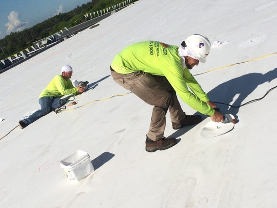 Two Crowther Roofing workers install fasteners by heat