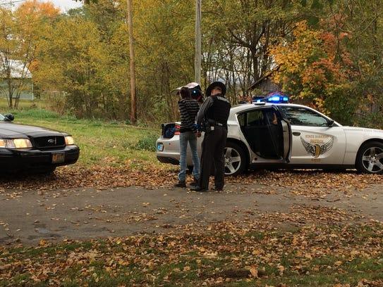 An Ohio Highway Patrol trooper detains a female passenger