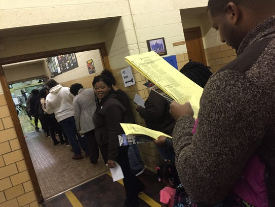 Voters  survey over a mock ballot as they stand in line