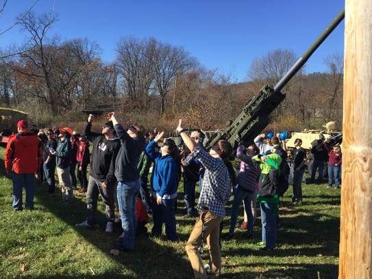 A crowd of students and teachers observe a pumpkin-slinging