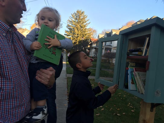 18-month-old Simon and Max, 9, check out the books