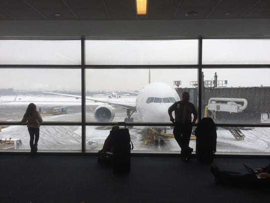 Travelers look out at winter weather conditions from
