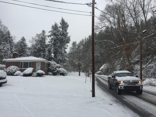 A truck traverses a snowy road in Marshall Saturday