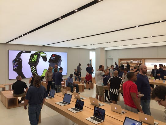 Customers check out a refreshed and expanded Apple