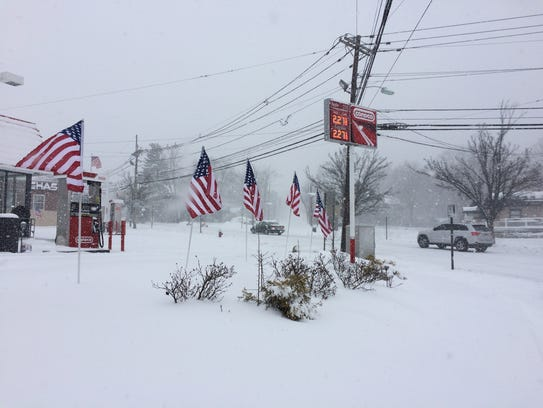 Flags blow in the wind and snow in Midland Park.