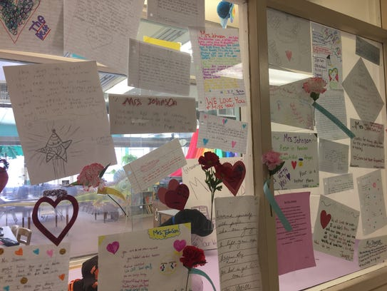 Cards of grief and condolences from students are displayed