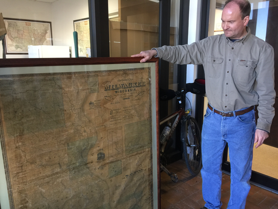 Tony Swain stands next to a map of Milwaukee County