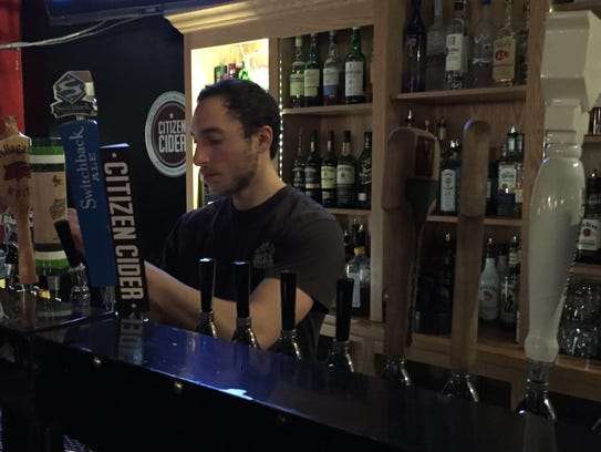 Joseph Collier fills a customer's beer order Monday