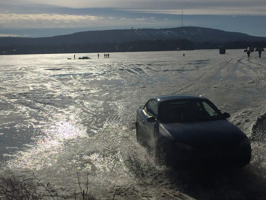 A car leaves the ice of the Wisconsin River after a