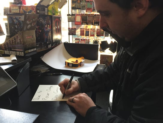 Dire Comics store owner Kyle Hearn writes up a sign