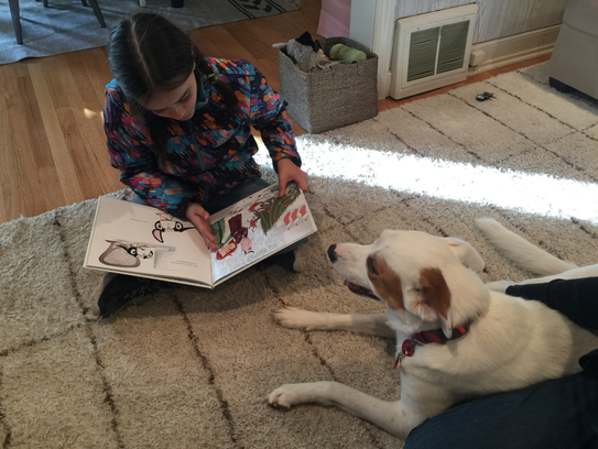 Nine-year-old Emma reads aloud to Autumn, a therapy