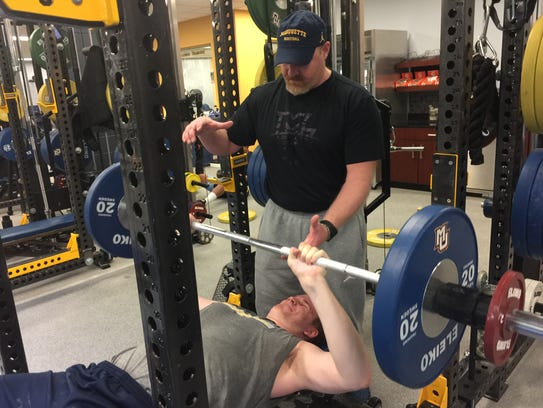 Todd Smith works with Marquette men's basketball player