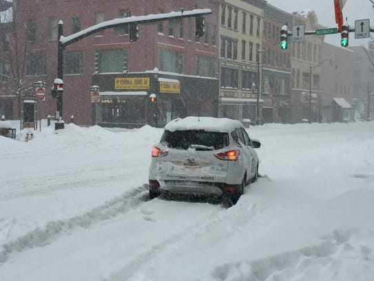 A sport utility vehicle gets stuck in snow in Downtown Binghamton in March. Experts suggest packing a winter preparedness kit for the car in case you become stranded.