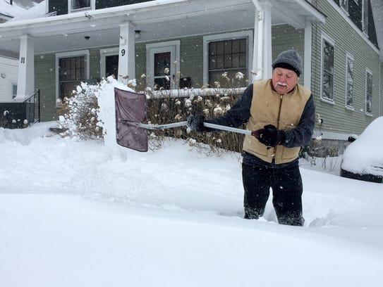 Dave Taft of South Burlington shovels the walk outside