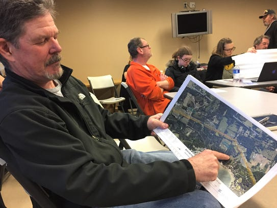 Pinckney resident Mark Redies points out on a map where