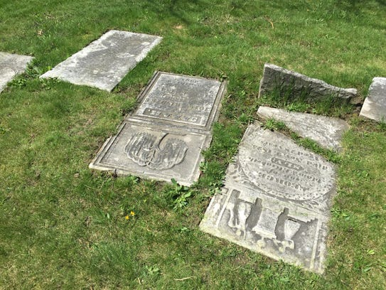 Intricate headstones lay on the ground of Elmira's