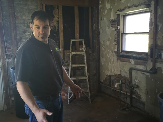 Dennis Delor looks around a kitchen being restored