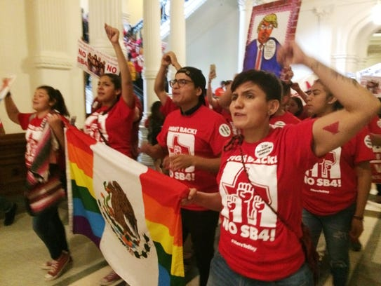Demonstrators march in the Texas Capitol on May 29,