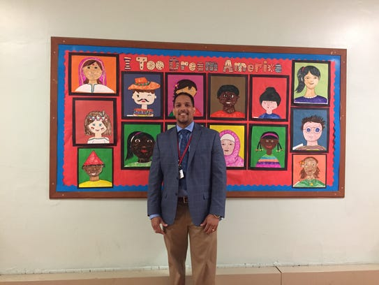 Jose Ramos stands in front of a student mural at Cramer