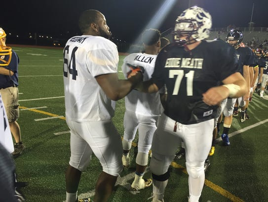 Two linemen shake hands after the 2015 Eddie Meath