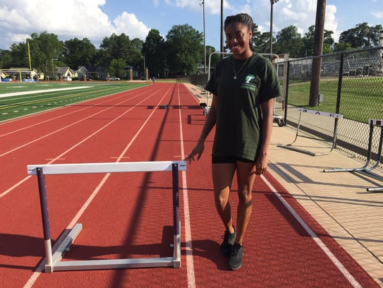 Byrd's Kyah Loyd stands next to a hurdle at the Byrd