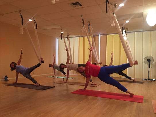 Jenn Smith, right, leads an aerial yoga practice at