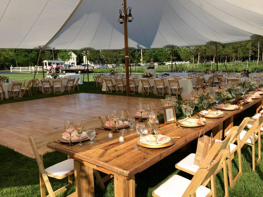 A sailcloth tent covers tables and a dance floor ready