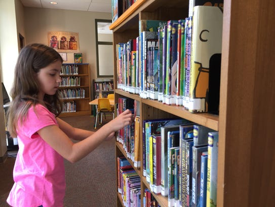 Mackenzie Kocacs, 11, checks out books available in