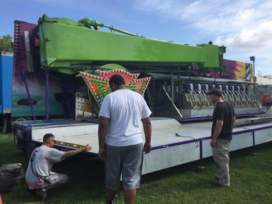 Bates Amusement employees set up rides at Muskingum