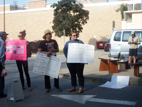 Protesters hold protest signs in front of Jeff Pierce's