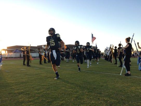 Gunner Cruz leads Queen Creek Casteel onto the field