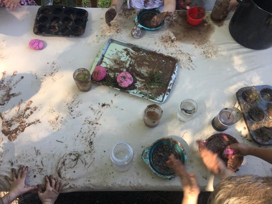Children making imaginary food out of mud as part of