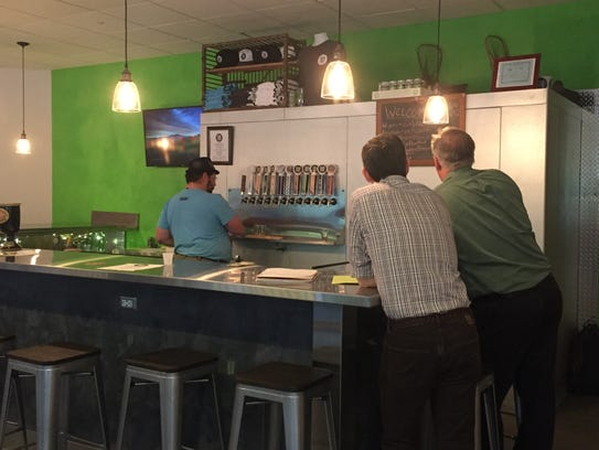 J. Burke Morrison pours beers for two customers at