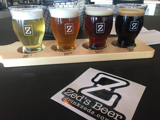 A flight of Zed's Beer sits on a bistro table at the