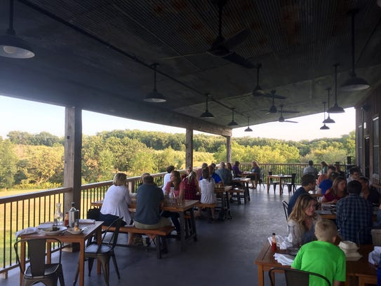 Diners sit on the porch at Rapid Creek Cidery, which
