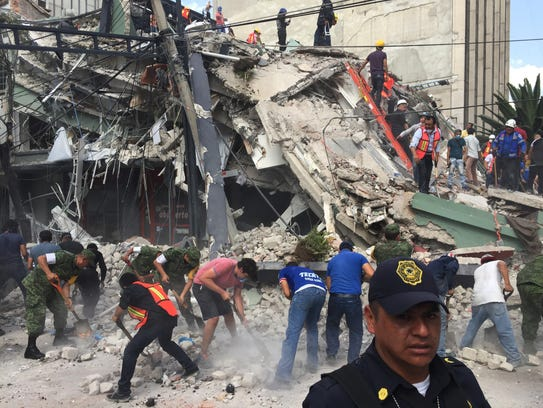 People search for survivors in a collapsed building
