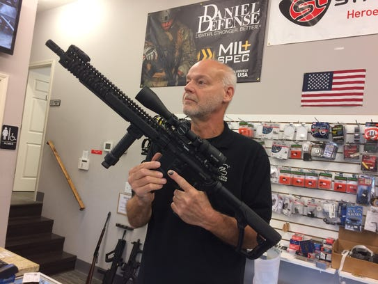 Mark Crabtree holds an AR-15 assault rifle at Guns