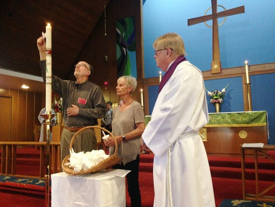 Peter Bowers (left) takes a flame from a paschal candle,
