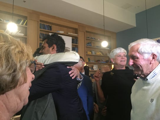 Democrat Vin Gopal embraces an attendee at his election