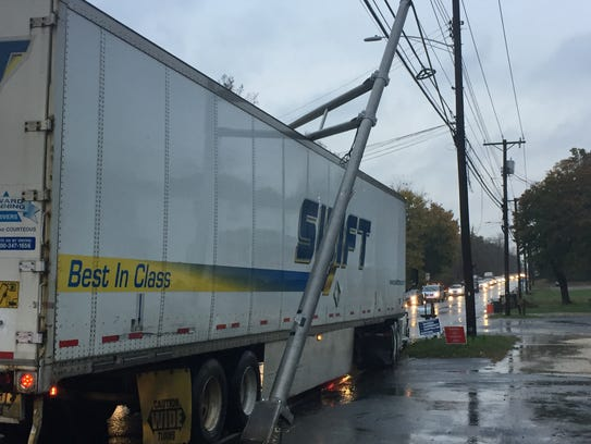 A tractor-trailer driver pulls to the side of Main Road in Vineland after ripping a traffic light from its base.
