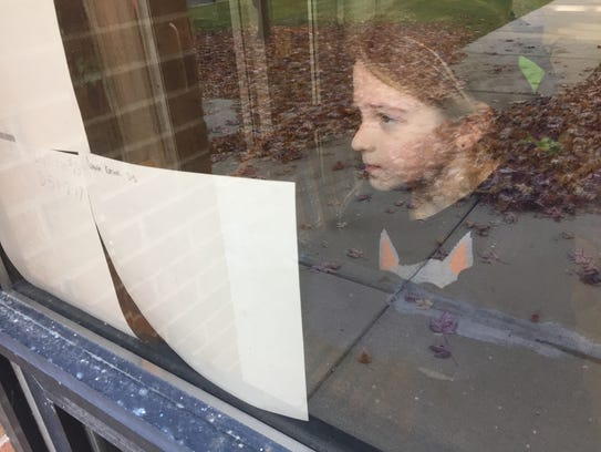 Alyssa Schafer, 10, posts a picture on a window at
