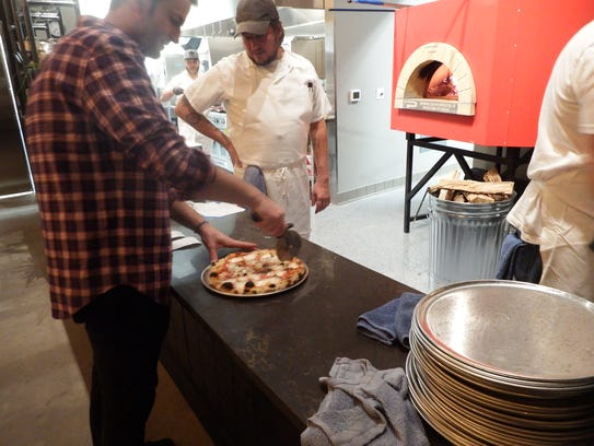 Marquee Pizzeria co-owner Sam Hall cuts a Margherita