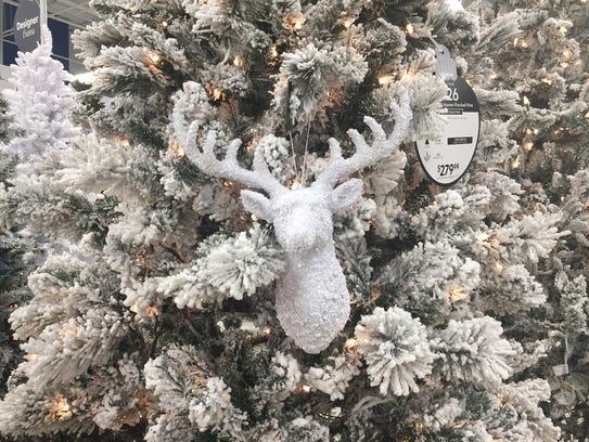 A reindeer head decorates a flocked tree on display