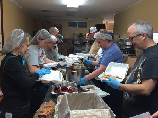 Volunteers assemble plates for delivery on Thanksgiving