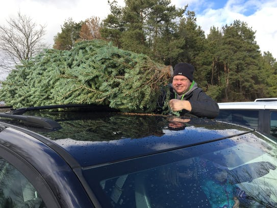 John Champagne, of Chesterfield Township, ties a Christmas