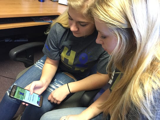 Maggie Andrews and Keely Drummond scroll through the #LetsTalk app they are promoting for teen with Alliance for Youth.