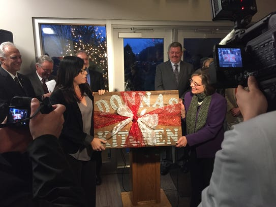 """Cornell Cooperative Extension Executive Director Victoria Giarratano presents Assemblywoman Donna Lupardo with a sign declaring the kitchen of the newly opened Taste NY Market """"Donna's Kitchen."""""""