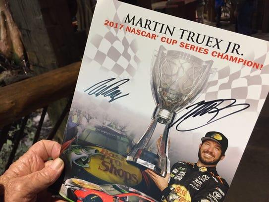 Racing fan Ron Arthur shows Martin Truex Jr.'s autograph